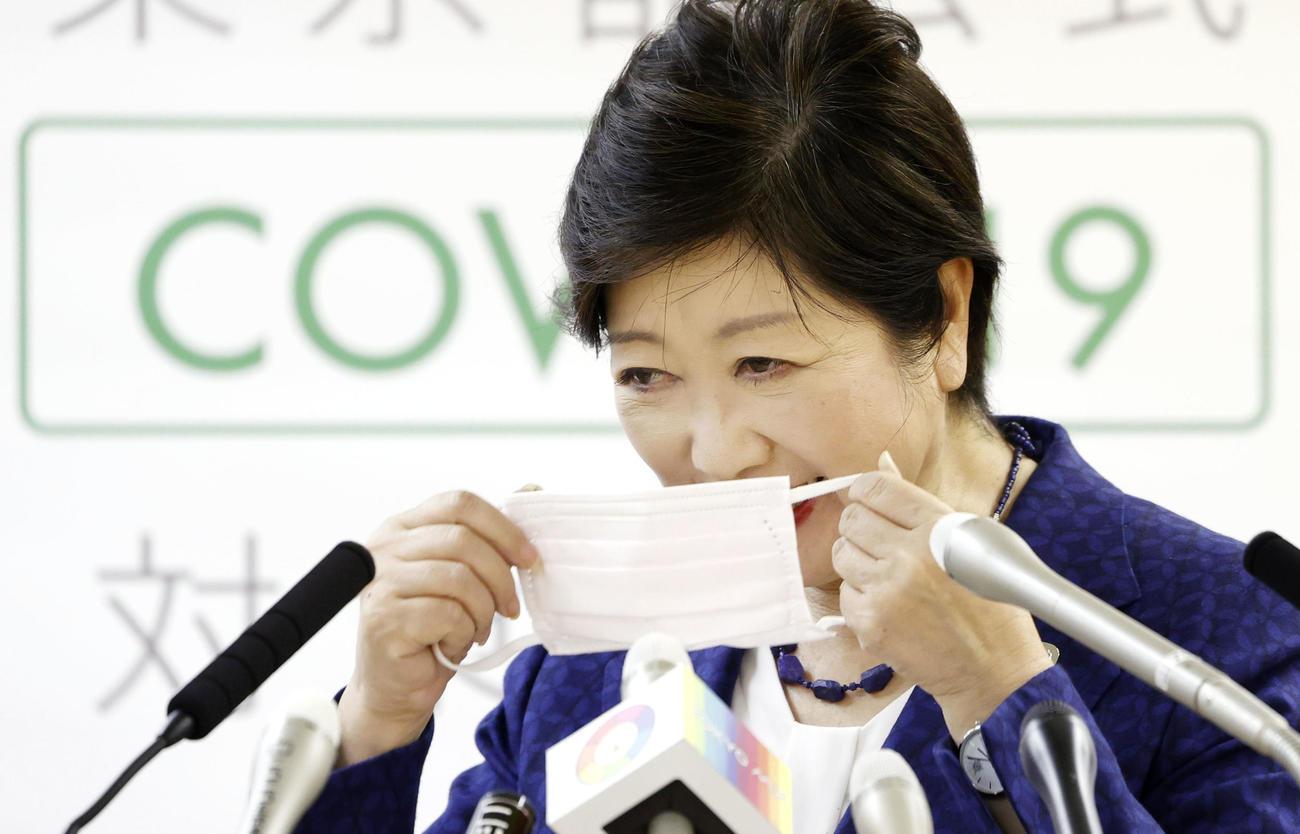 記者会見の途中でマスクを着け直す東京都の小池百合子知事(共同)