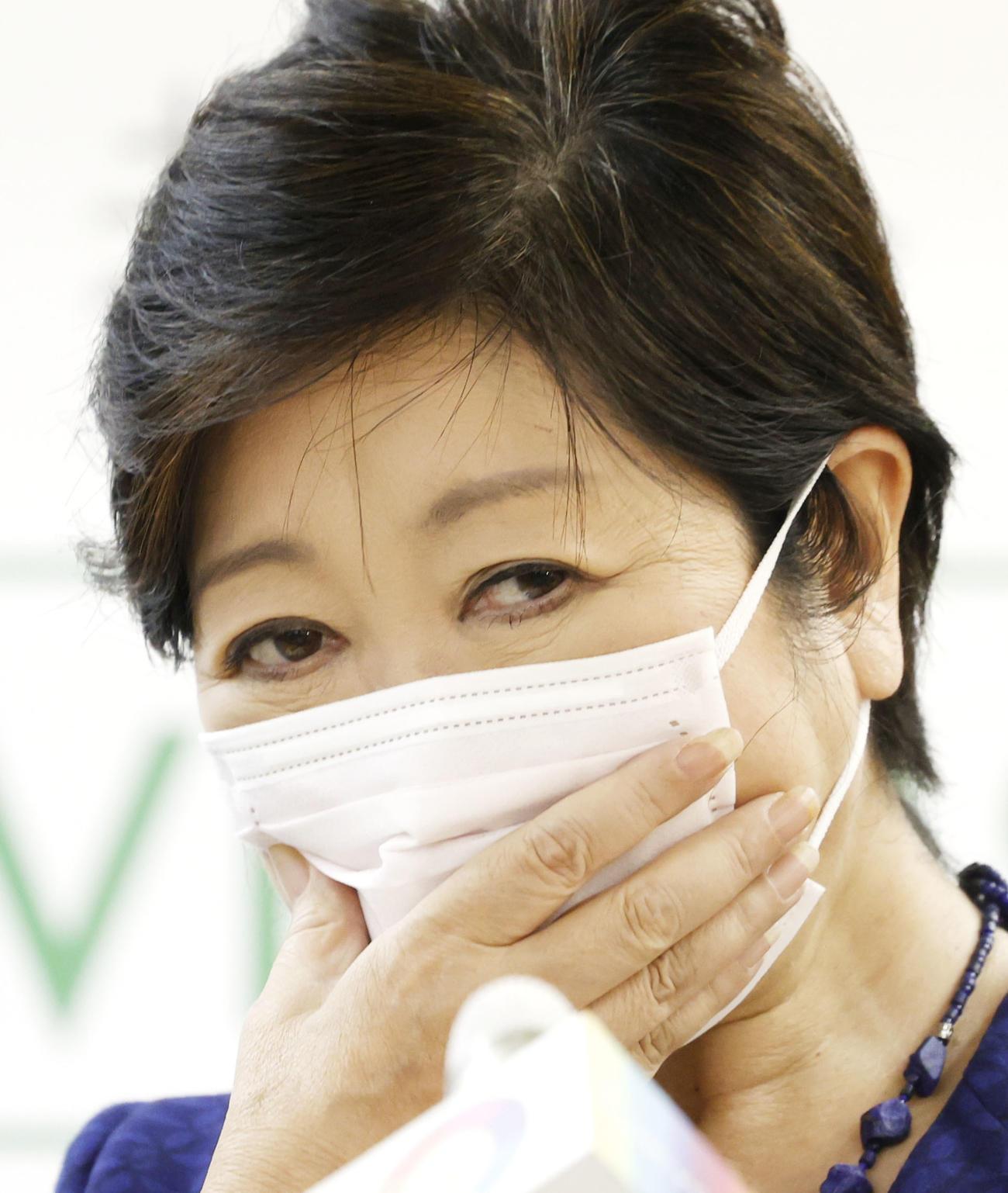 記者会見の途中でマスクに手をやる東京都の小池百合子知事(共同)