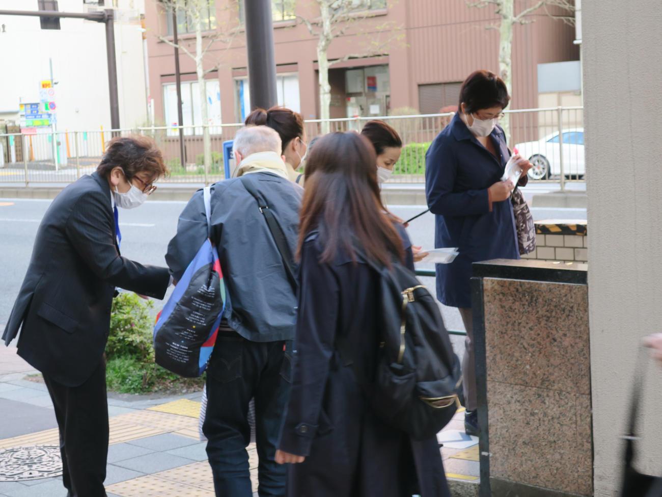 東京メトロ築地駅でマスクを配布するボランティアの男性(左)