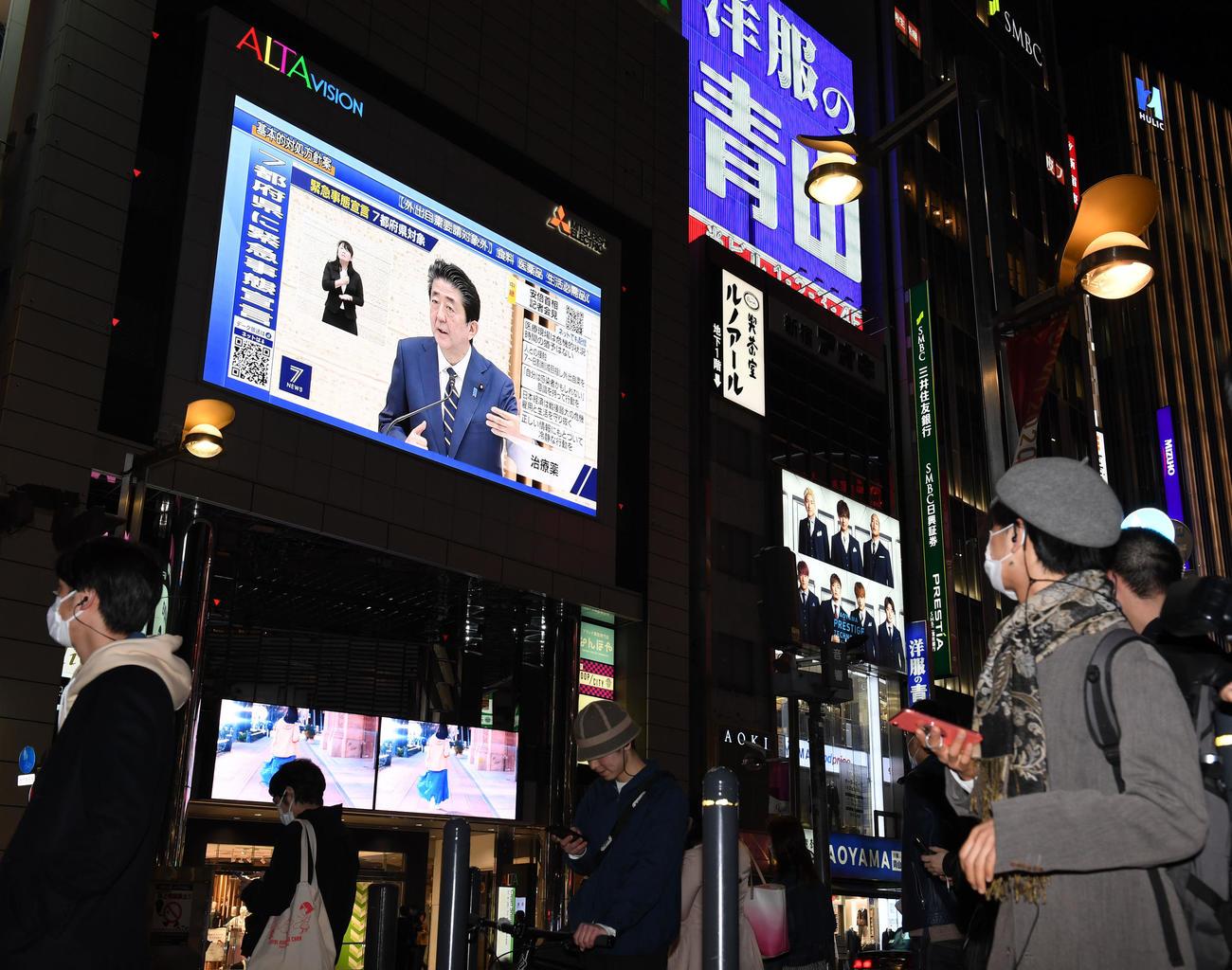 緊急事態宣言が発令され、安倍首相の会見を映す新宿駅東口の大型モニター(撮影・横山健太)