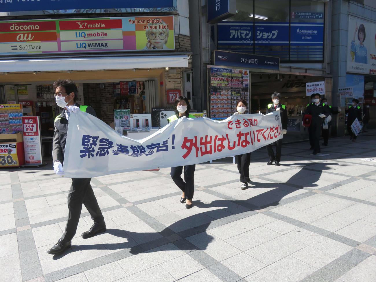 吉祥寺のアーケード街などで武蔵野市の職員らが外出自粛を求める横断幕を手に注意喚起した(撮影・大上悟)