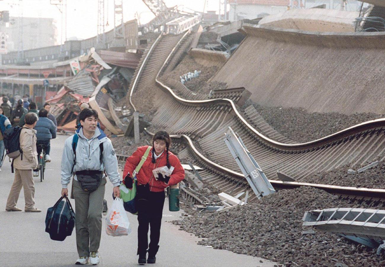 横倒しになった私鉄の高架線路脇を歩いて物資を運ぶ被災者(撮影・宮崎幸一)