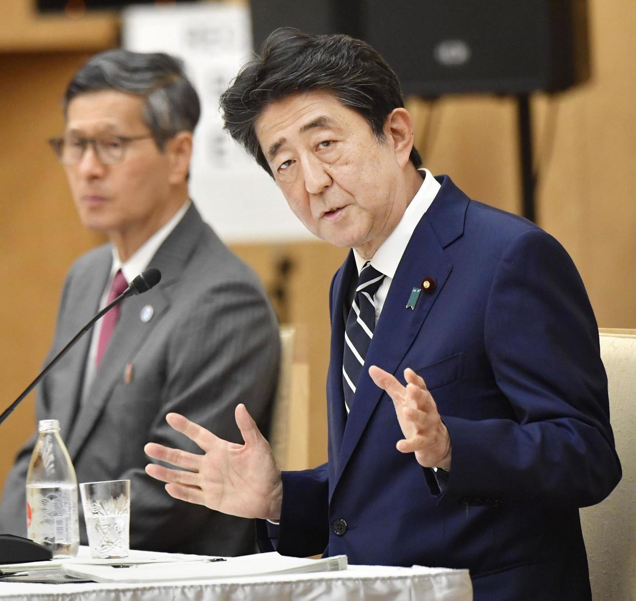 新型コロナウイルス特措法に基づく緊急事態宣言全面解除について記者会見する安倍首相(右)(共同)