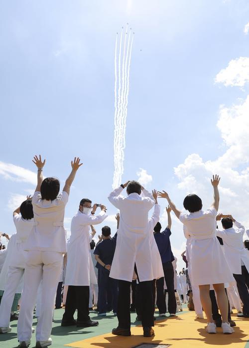医療従事者に敬意を示すため、自衛隊中央病院の上空を飛行するブルーインパルス(共同)