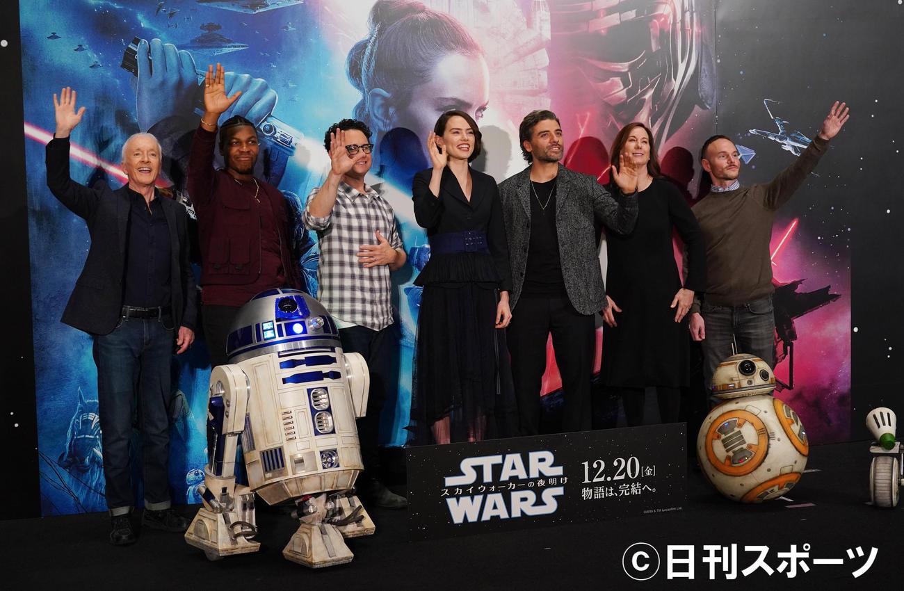 映画「スター・ウォーズ/スカイウォーカーの夜明け」のキャストらの来日記者会見でカメラに向かって手を振る、左からアンソニー・ダニエルズ、ジョン・ボイエガ、J.J.エイブラムス監督、デイジー・リドリー、オスカー・アイザック、プロデューサーのミシェル・レイワン氏、脚本のクリス・テリオ氏(2019年12月12日撮影)