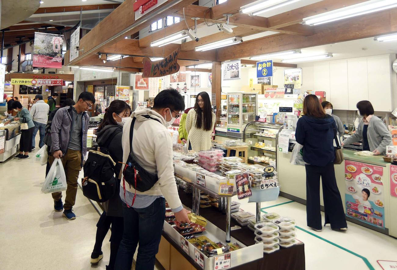 道の駅内の売店で買い物を楽しむ観光客