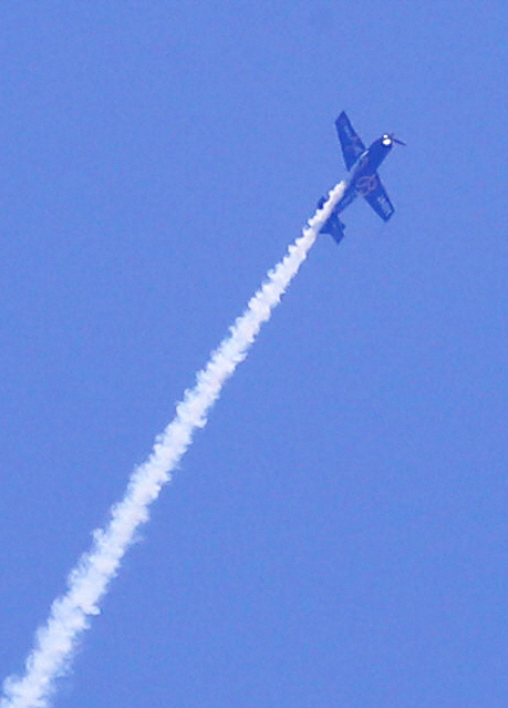福島の青空に描いたにこちゃんマークを描きエアロバティックパイロットの室屋義秀さんが乗ったプロペラ機(撮影・野上伸悟)