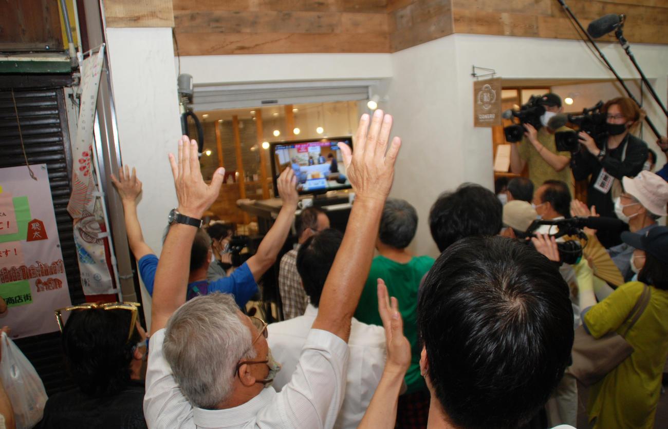 藤井聡太七段勝利の瞬間、愛知県瀬戸市にある「せと銀座通り商店街」の店頭に置かれたテレビの前の地元ファンはバンザイ(撮影・松浦隆司)