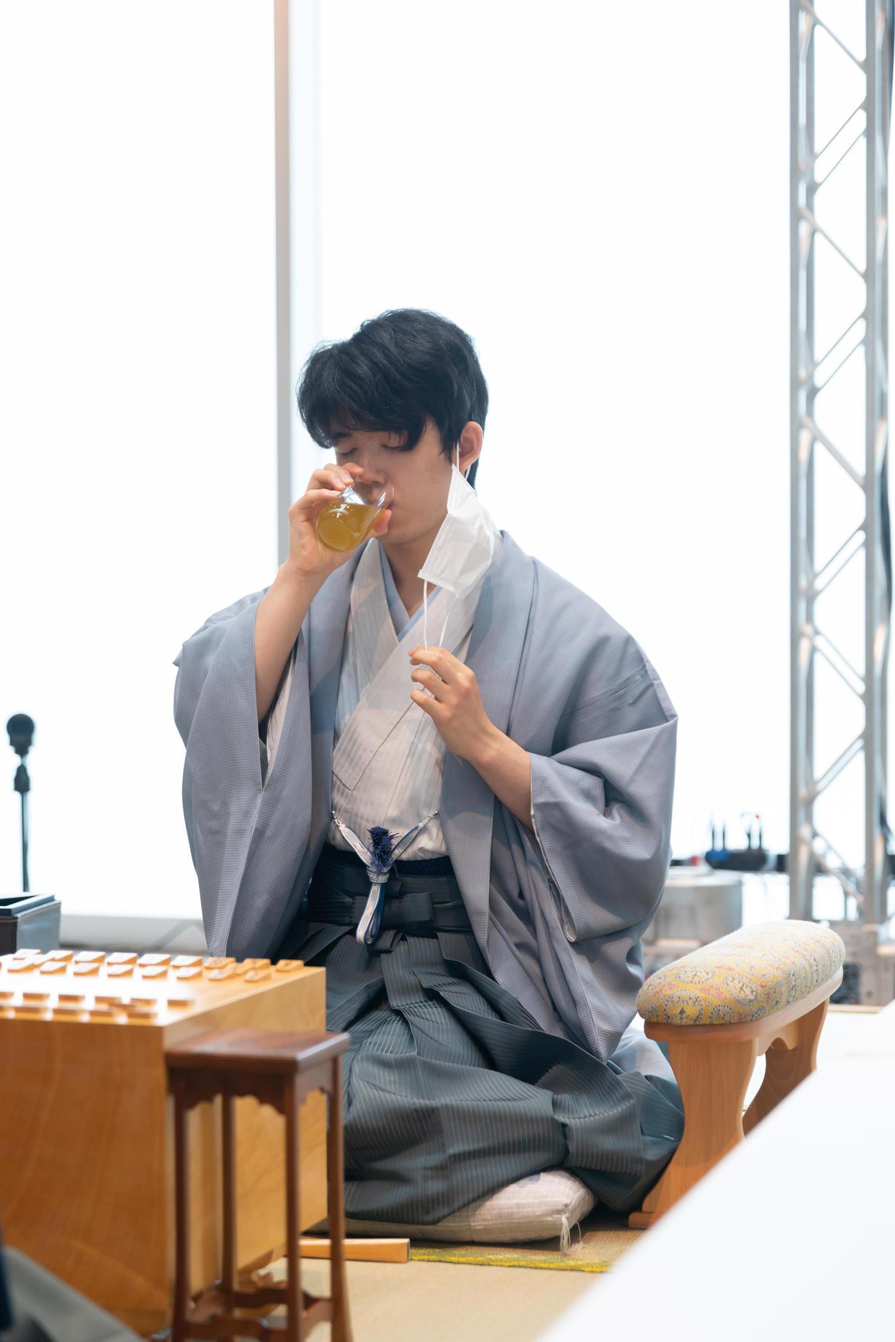 初手を指す前、お茶を一口飲む藤井聡太七段(日本将棋連盟提供)