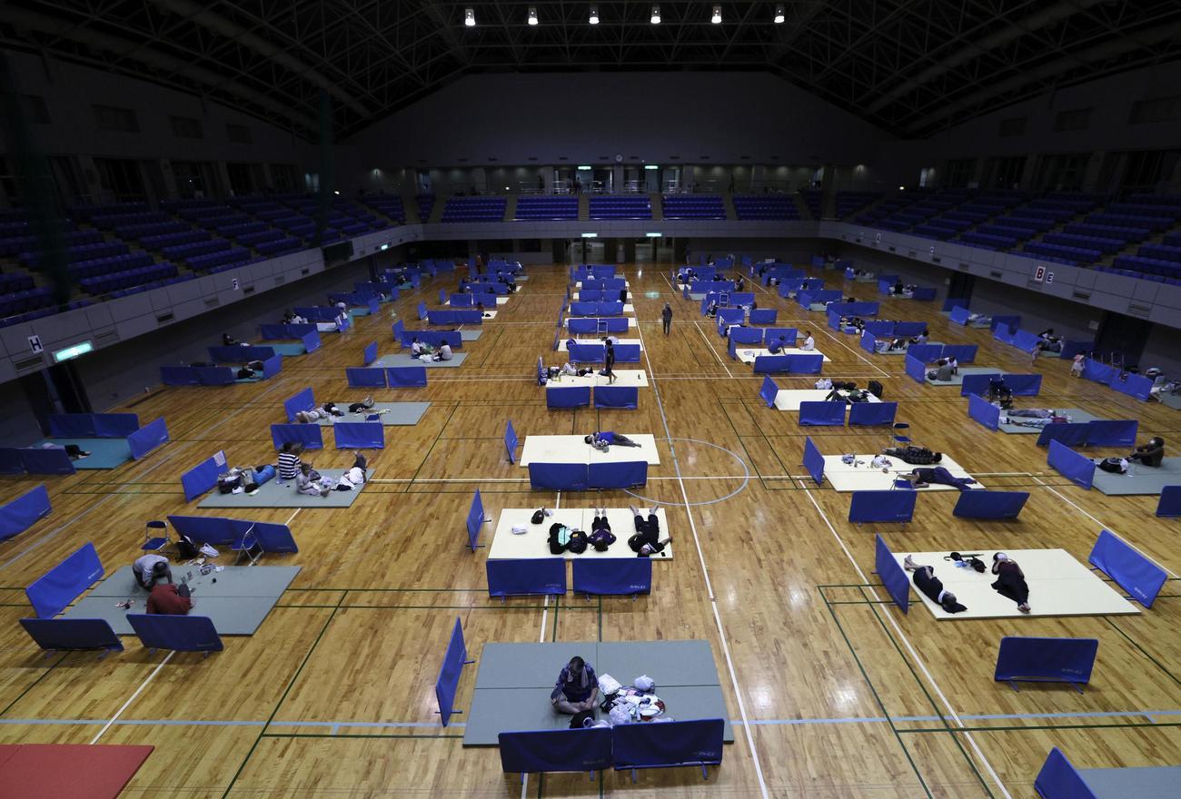 熊本県人吉市の避難所。新型コロナウイルス対策でマットの間隔を空けて配置していた(共同)