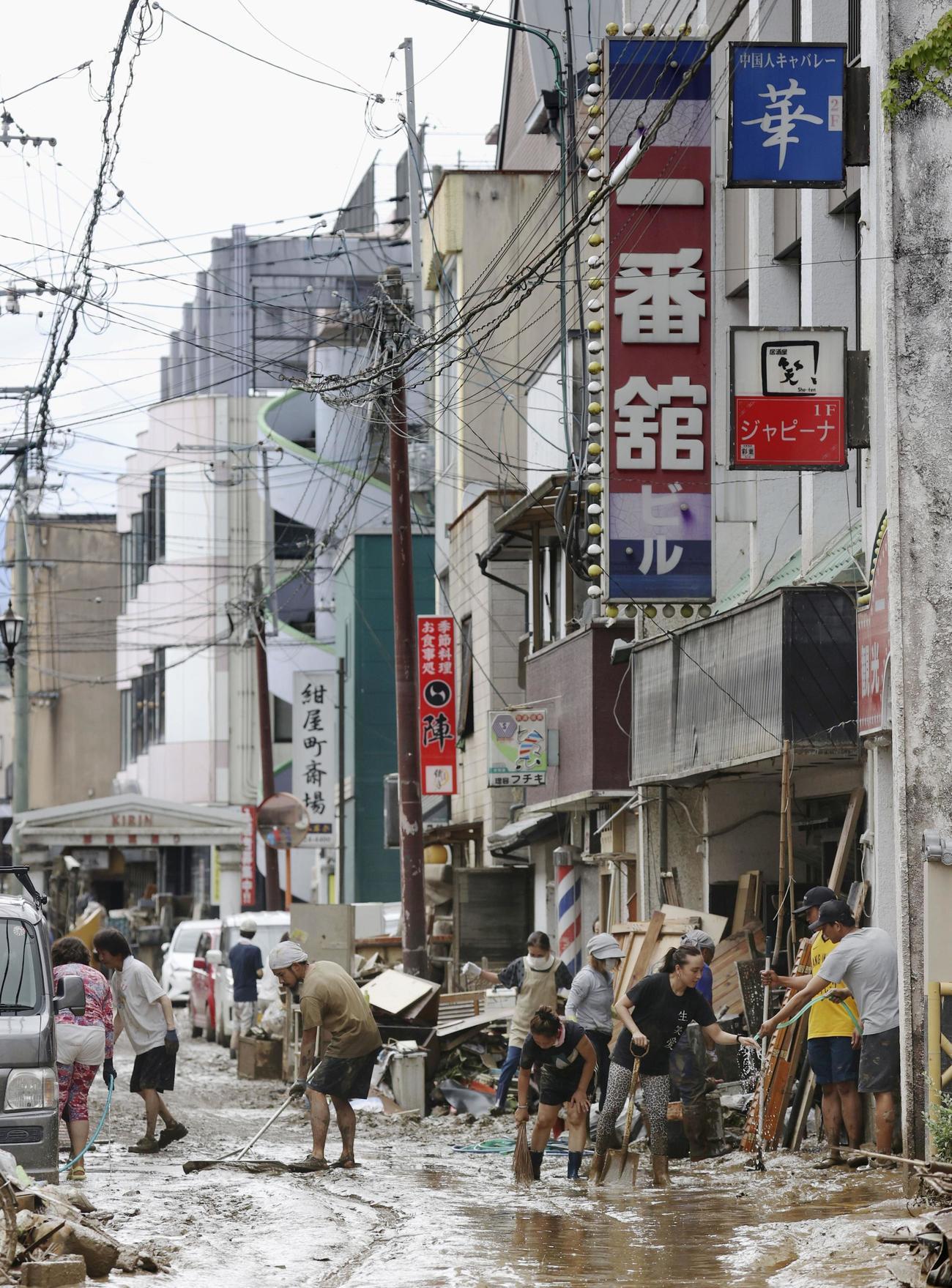 浸水被害のあった熊本県人吉市の市街地で片付けをする人たち(共同)