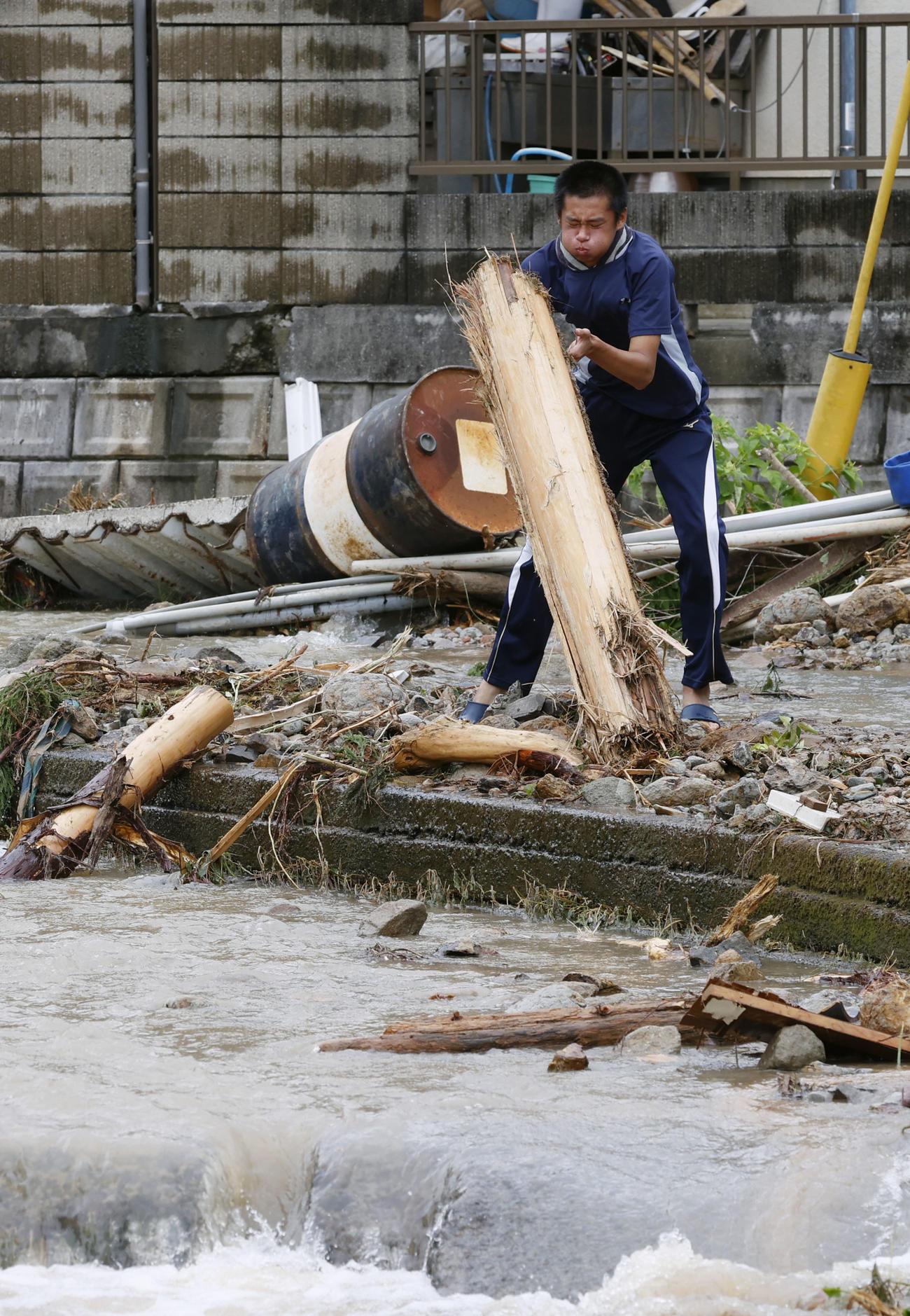 熊本県津奈木町で、倒木を片付ける男性(共同)