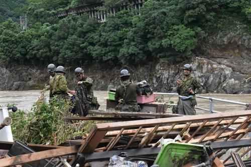 増水した球磨川の周辺で捜索にあたる自衛隊員(共同)