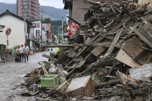浸水被害のあった熊本県人吉市の市街地で、道路脇に積まれたがれき(共同)