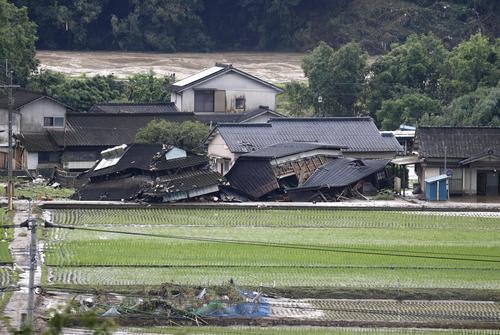 豪雨被害を受けた家屋。奥は増水した球磨川(共同)