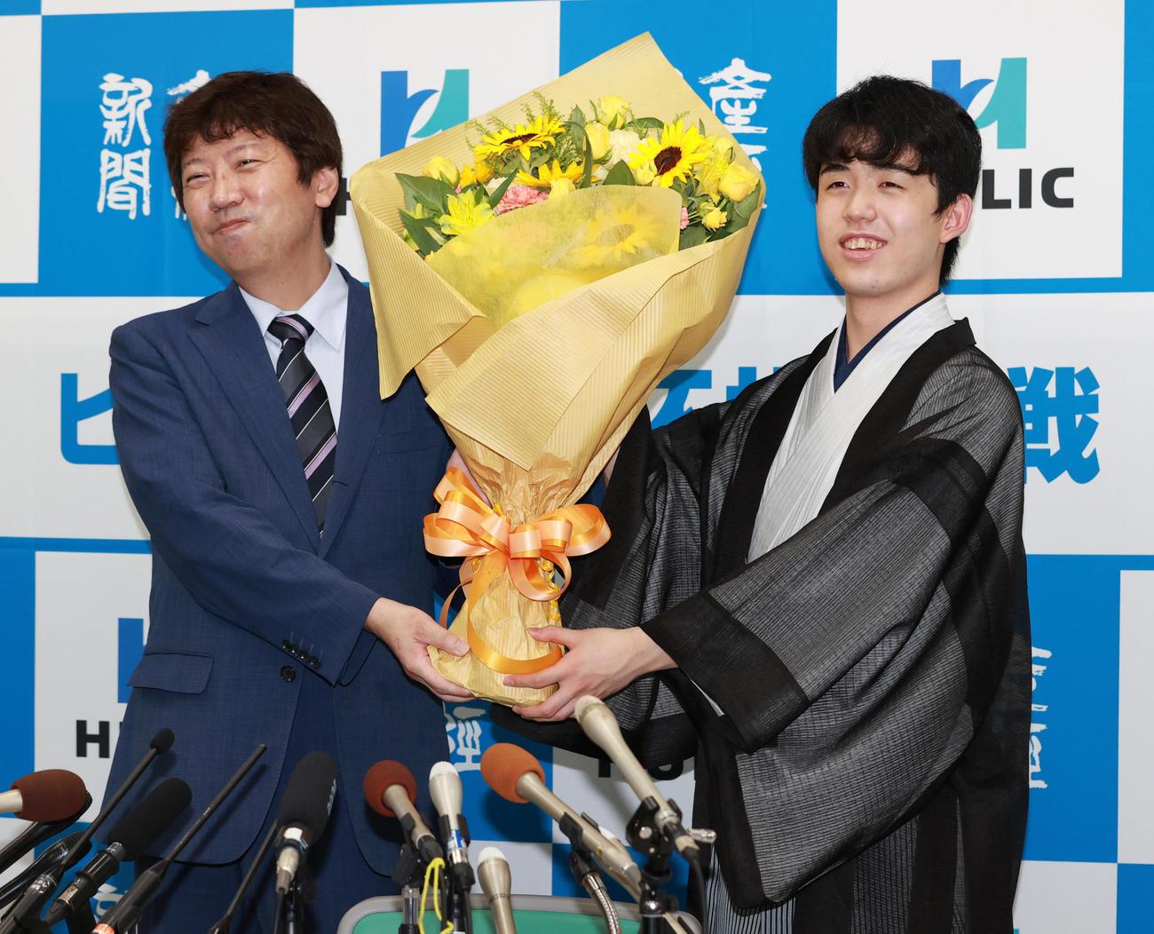 初タイトルを獲得し杉本昌隆八段(左)から花束を受け取る藤井聡太新棋聖(撮影・清水貴仁)