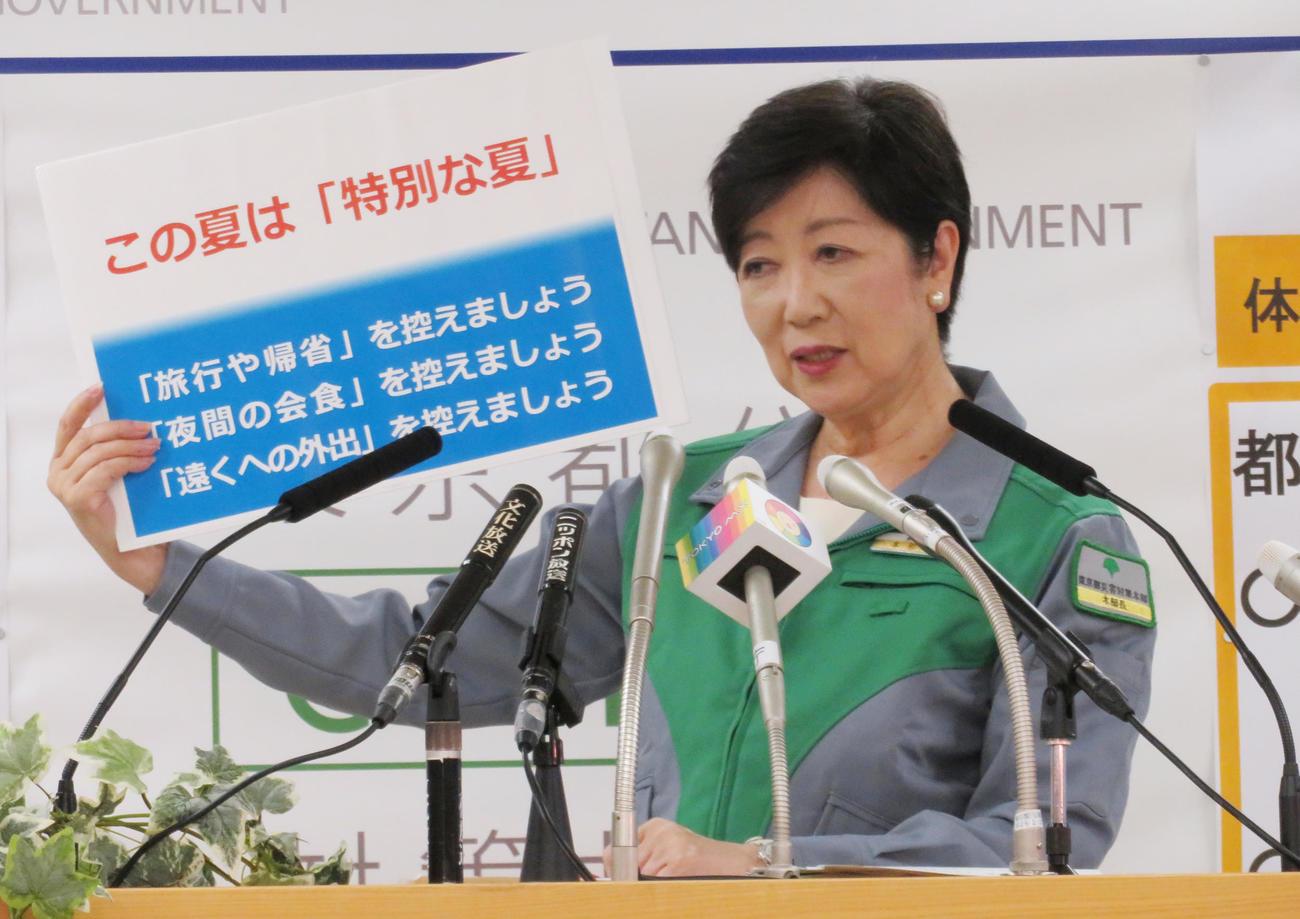 東京都の小池百合子知事は、ボードを持ち、夏の帰省などを控えるよう呼び掛けた(撮影・佐藤勝亮)