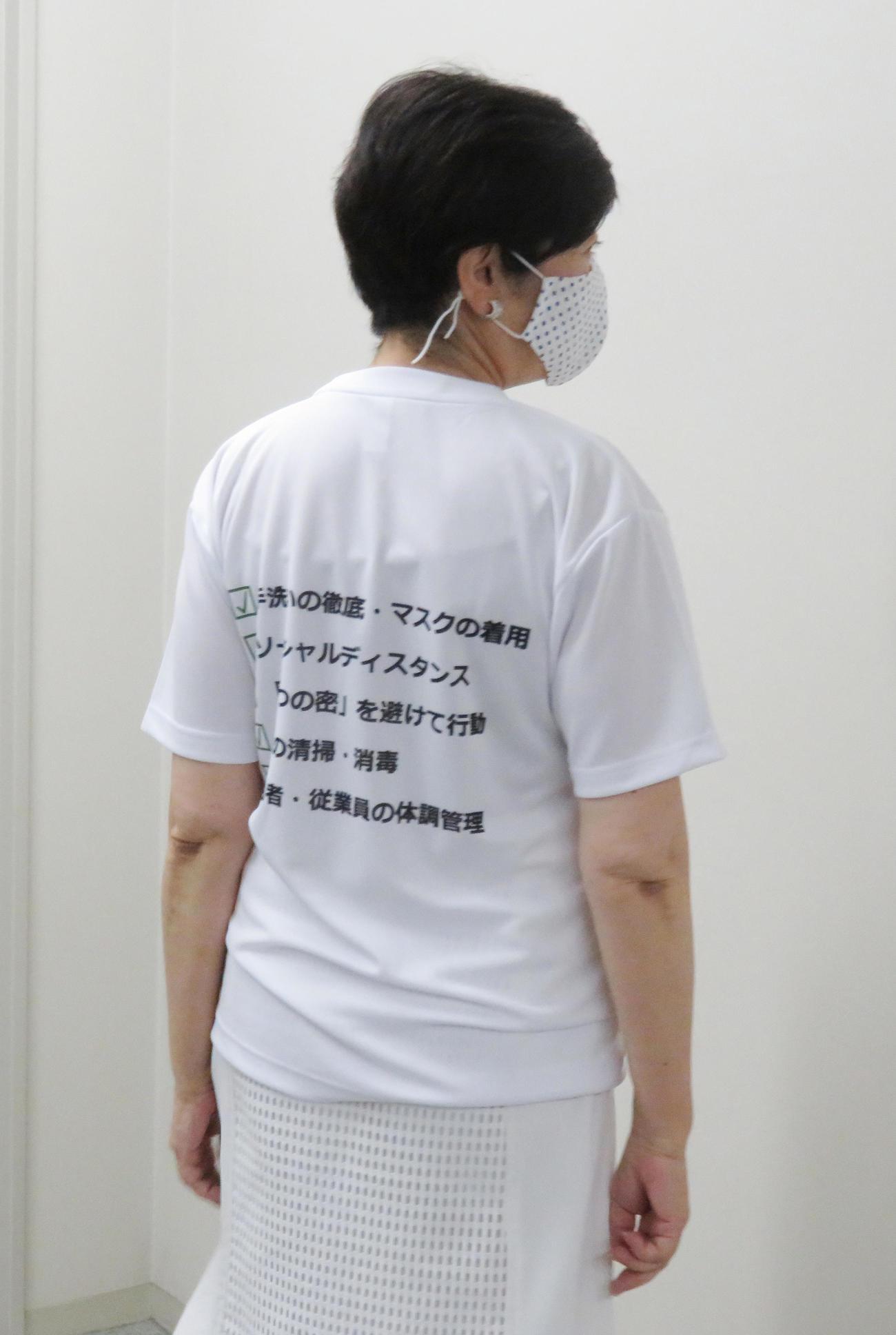 感染防止徹底宣言ステッカーがプリントされたTシャツを着用し、会見終了後、写真撮影に応じた東京都の小池百合子知事「後ろもあるのよ」(撮影・佐藤勝亮)
