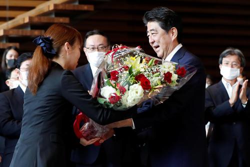 花束を渡されて首相官邸を見送られる安倍前首相(ロイター)