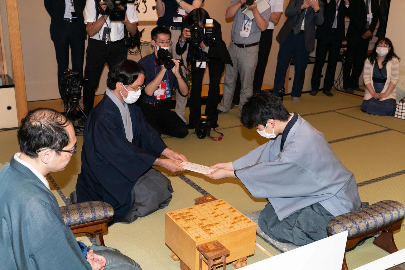 藤井聡太七段(右)が王位戦7番勝負第2局で初めて行った封じ手(中央は立会人の深浦康市九段、左は木村一基王位、段位・肩書は当時、日本将棋連盟提供)