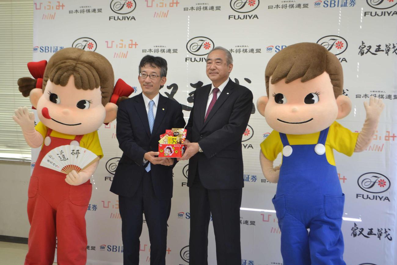 第6期叡王戦記者会見に出席した日本将棋連盟の佐藤康光会長(左)と不二家の河村宣行社長。左端が不二家マスコットキャラクターのペコちゃん、右端がポコちゃん