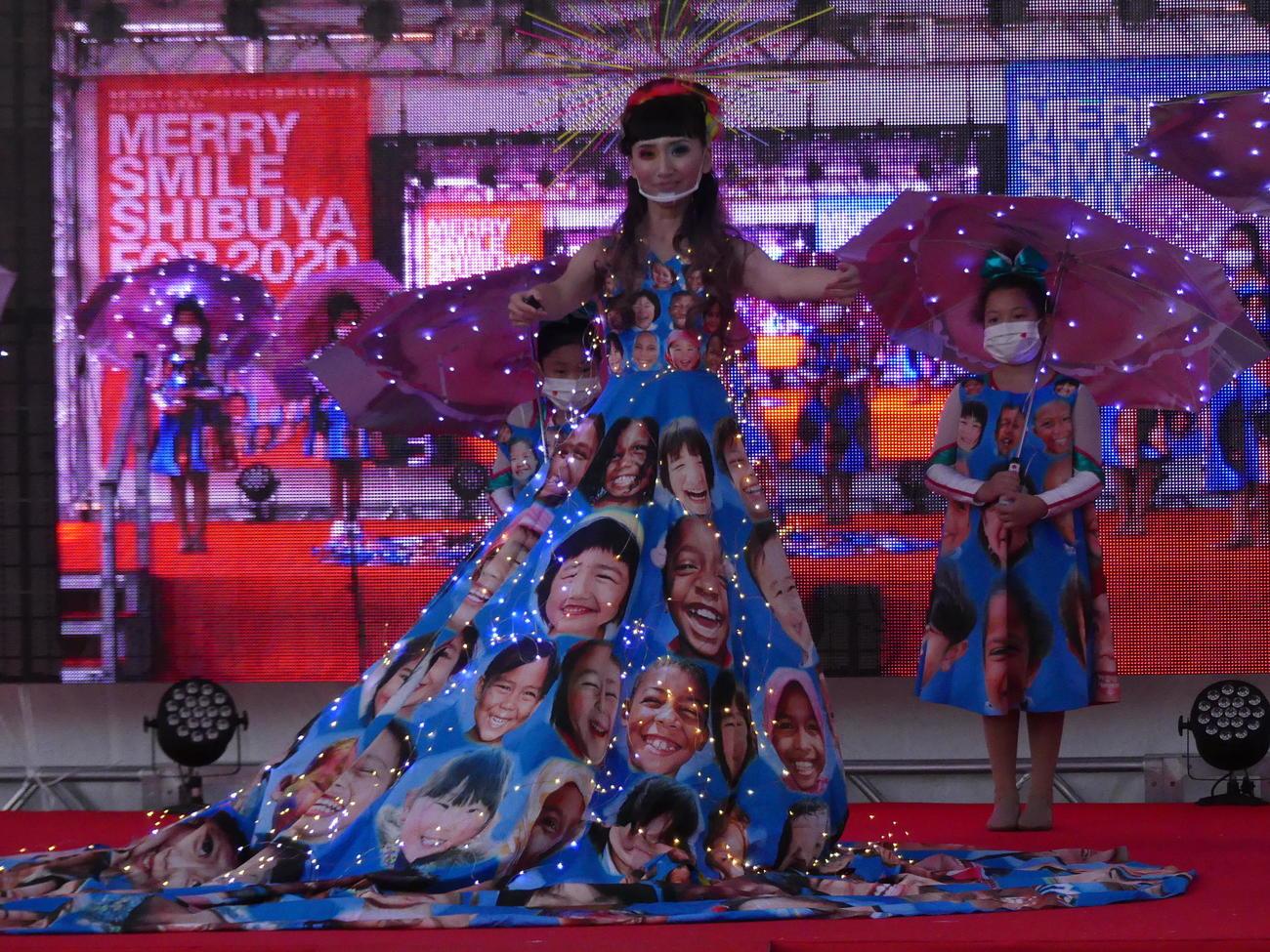 東京パラリンピックに向けた渋谷区文化プログラムで、夕暮れ時、LED電灯がちりばめられた「笑顔のドレス」が披露された