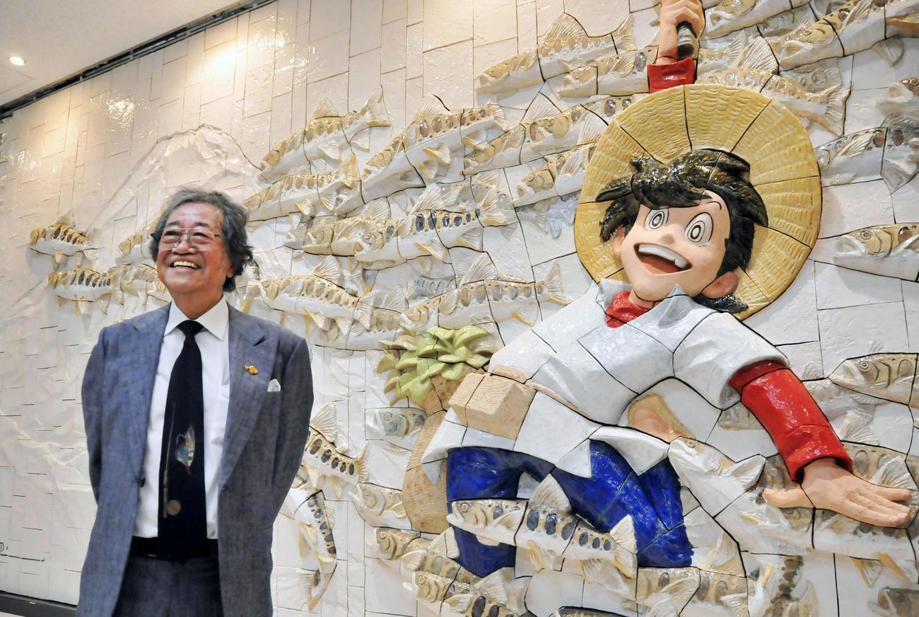 「釣りキチ三平」のレリーフの前で笑顔の矢口高雄さん=2016年10月、秋田空港(共同)