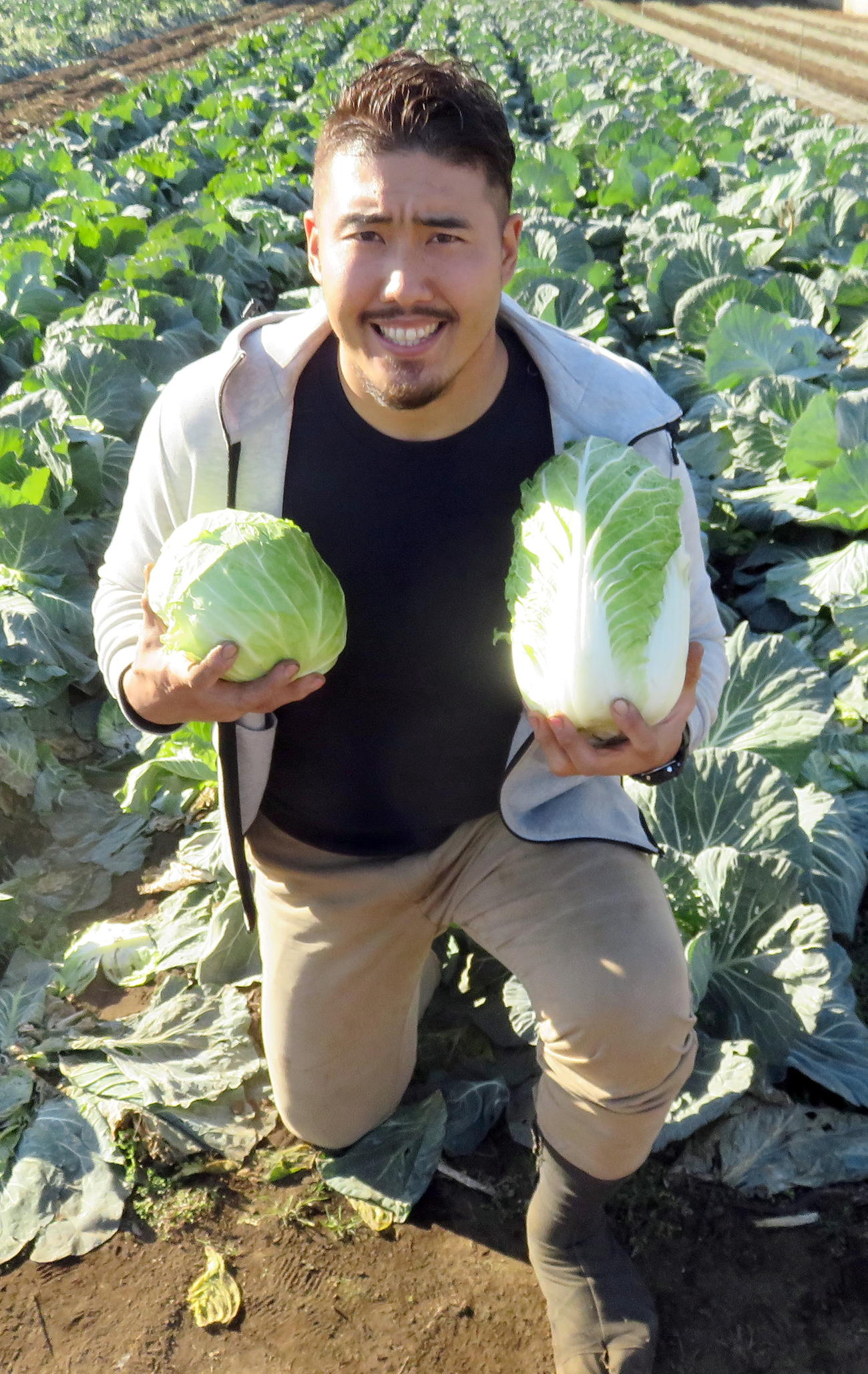 収穫したキャベツとアメリカンフットボールに似ている形の白菜を手に東京の農業発展を誓う岡田さん(撮影・鎌田直秀)