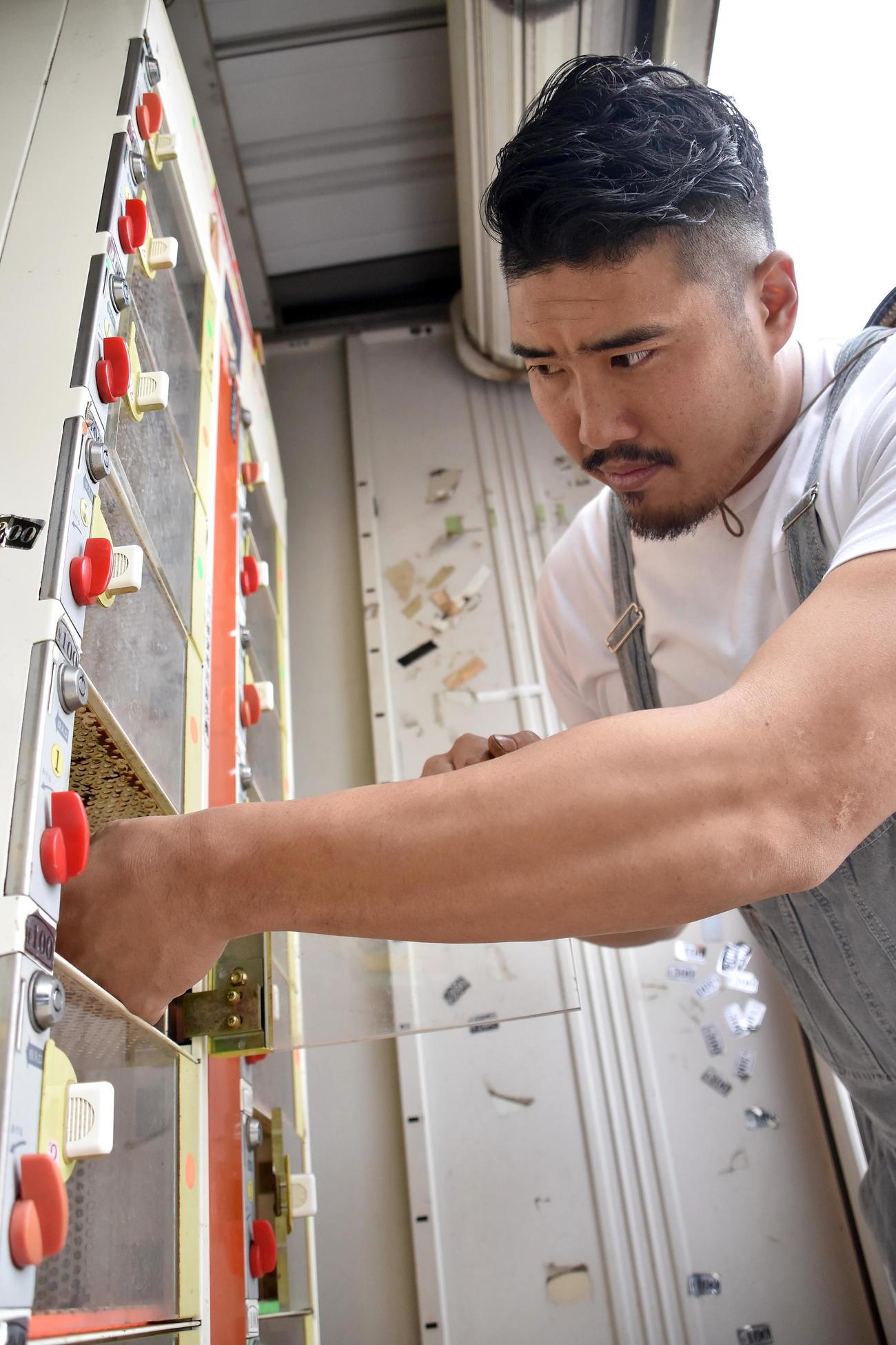 自動販売機に野菜を入れる岡田さん
