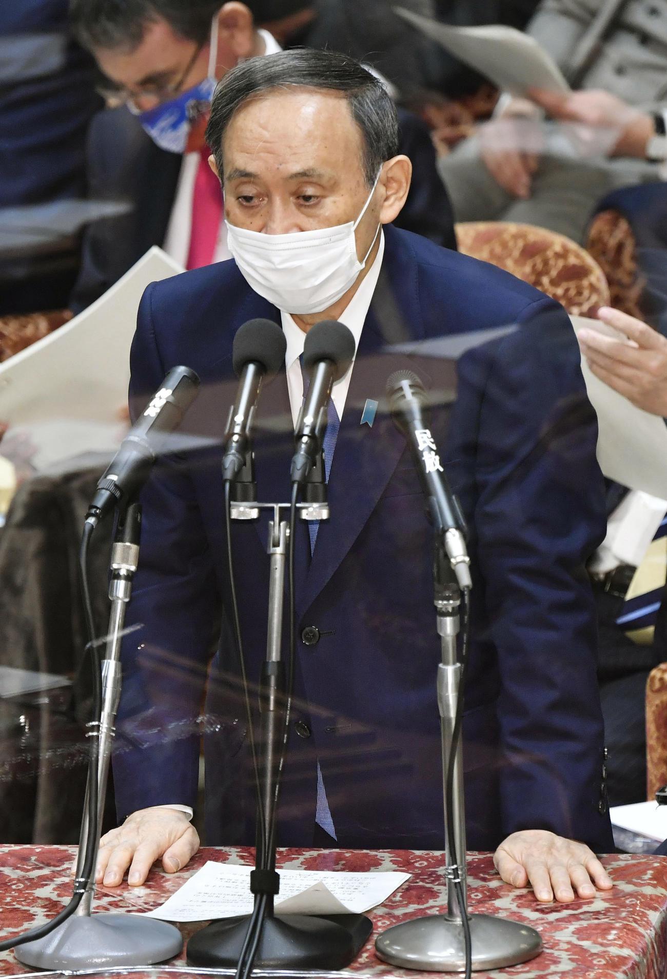 新型コロナ感染対策で置かれたアクリル板越しに、衆院予算委で答弁する菅首相(共同)