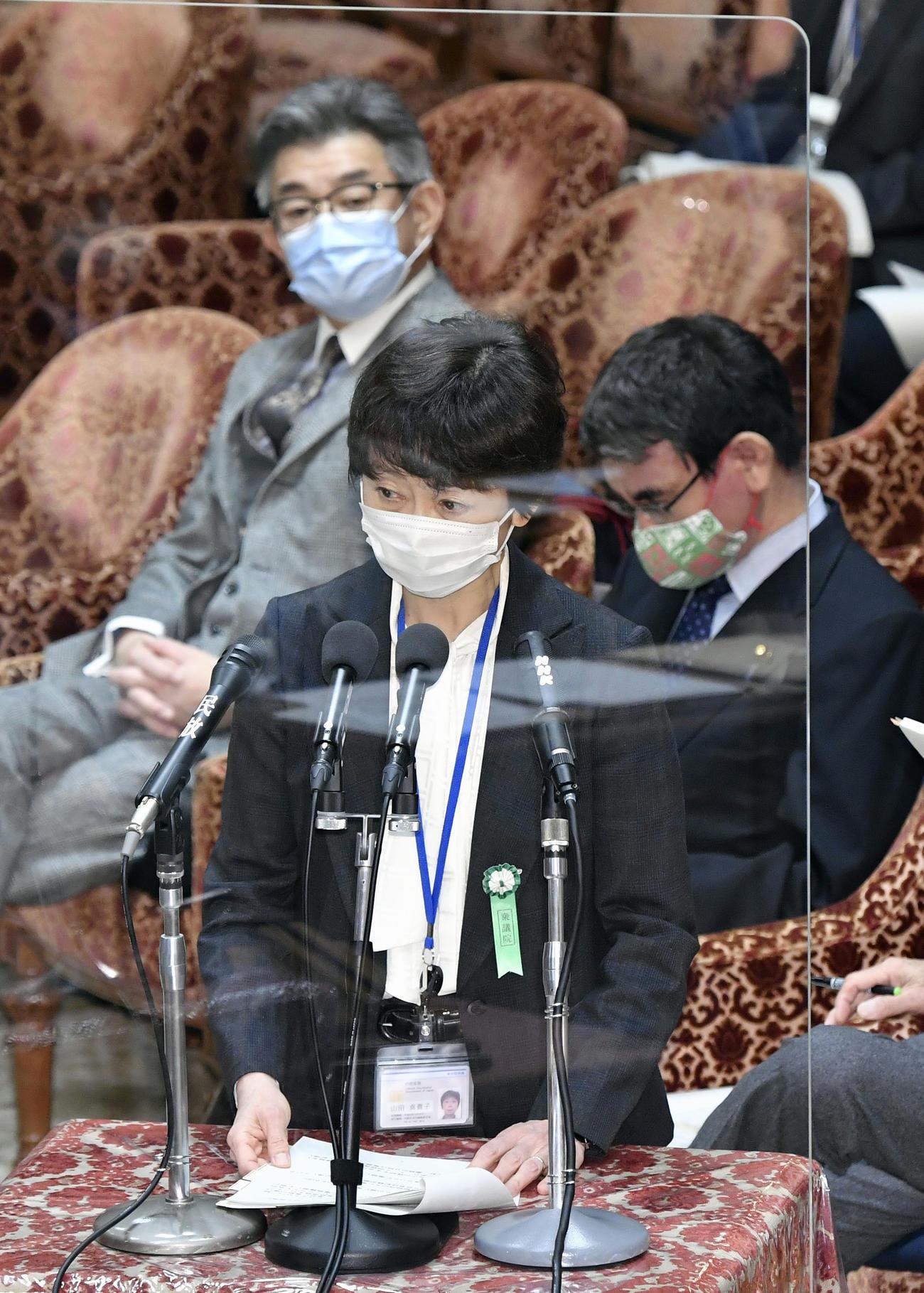 衆院予算委で答弁する山田真貴子内閣広報官。奥は武田総務相(共同)