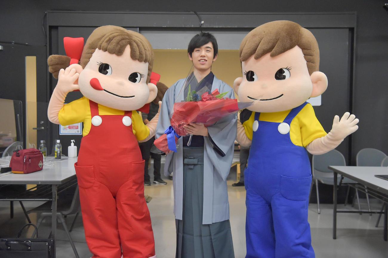 撮影後には、不二家のマスコットキャラクター「ペコちゃん」「ポコちゃん」から花束が贈られた藤井聡太2冠
