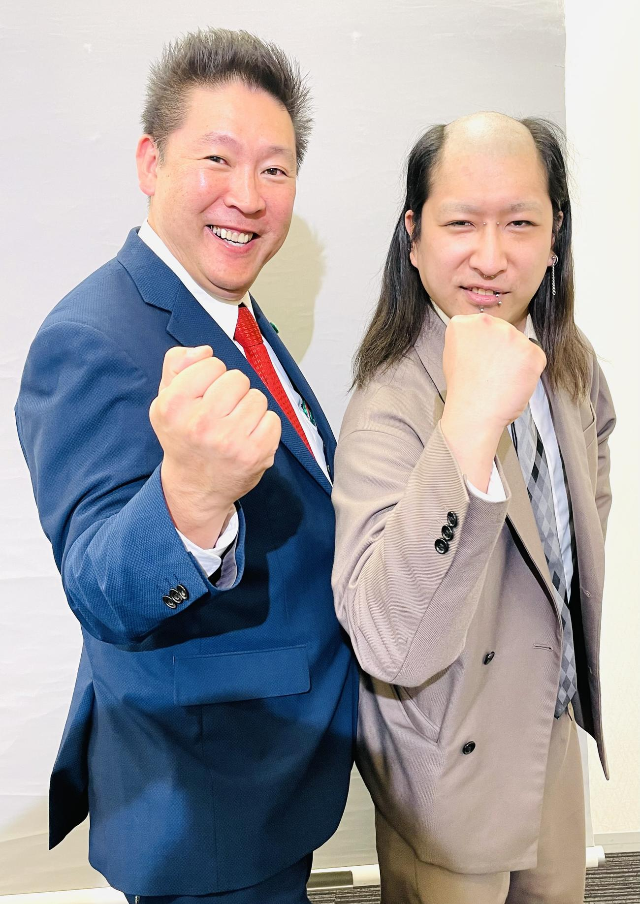 「今の政治にカツを入れる!」と力こぶをつくるNHK党の立花孝志党首(左)とYGこと矢島秀平氏