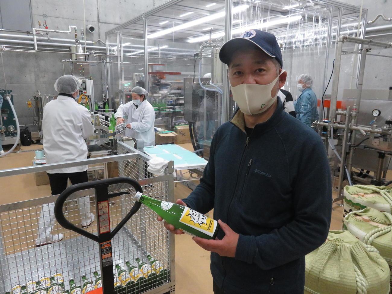 瓶詰めされた「磐城壽ランドマーク」を手に取る鈴木酒造店の社長で杜氏(とうじ)の鈴木大介さん