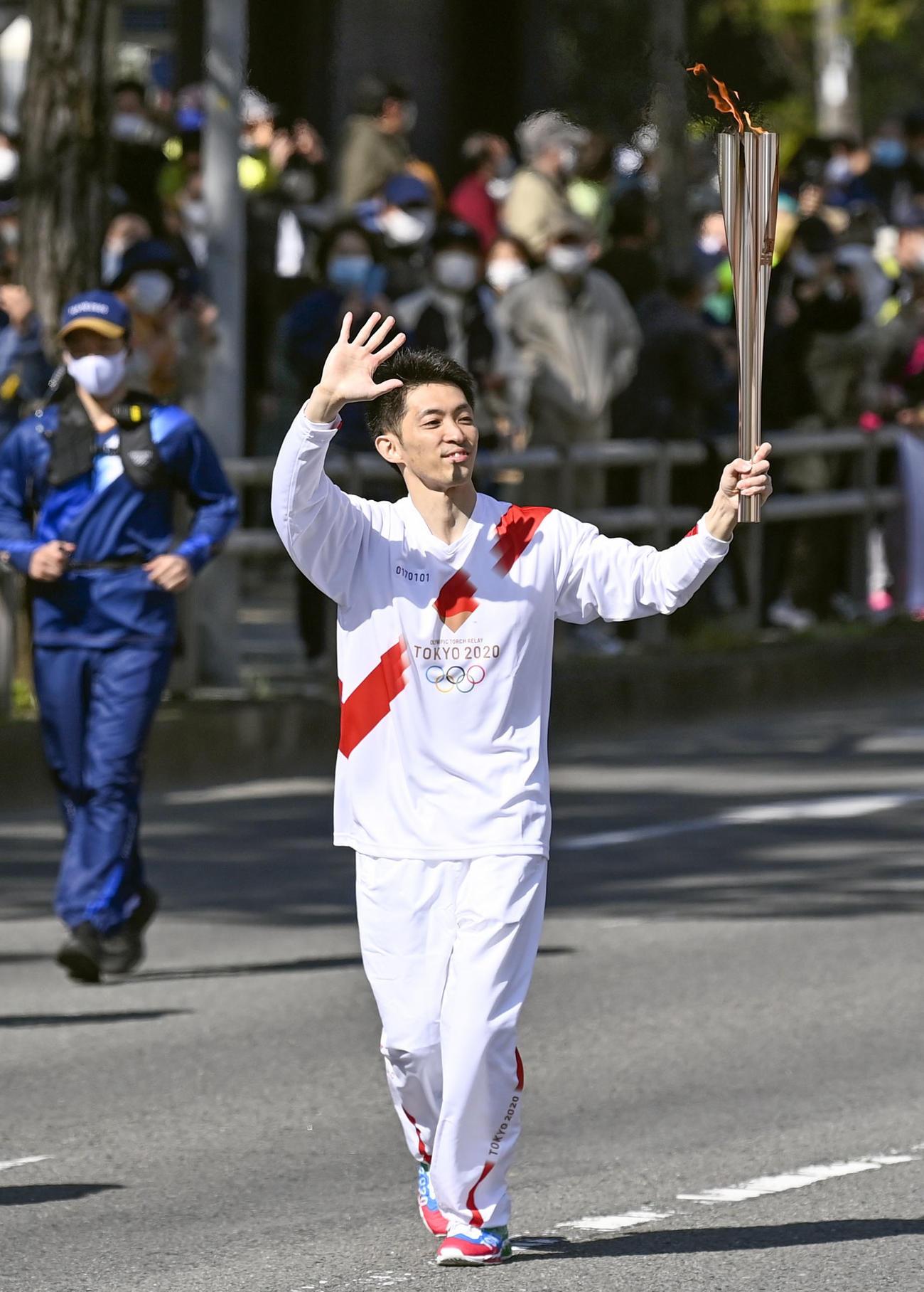 聖火のトーチを掲げて走る田中和仁さん(共同)