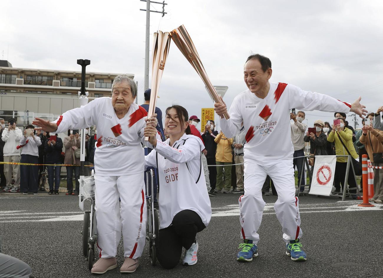 次走者に聖火を引き継ぐ109歳の賀川滋子さん(左)(共同)