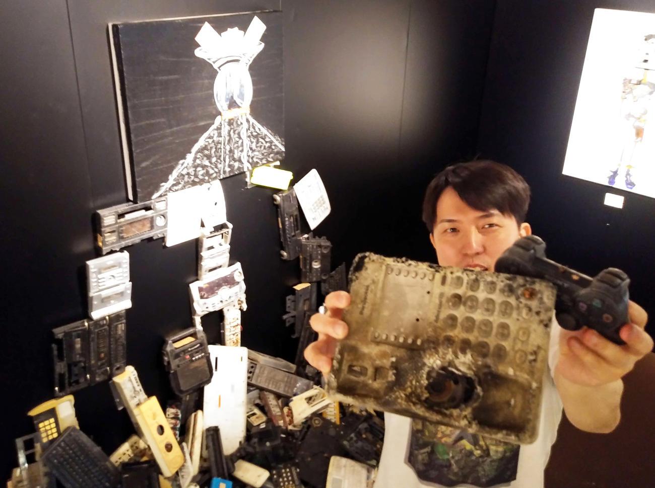 ガーナの電子機器廃材で、ほぼ即興でつくった作品「Capital to money]。MAGOさんの手には電話機とゲーム機の廃材が握られていた(撮影・寺沢卓)