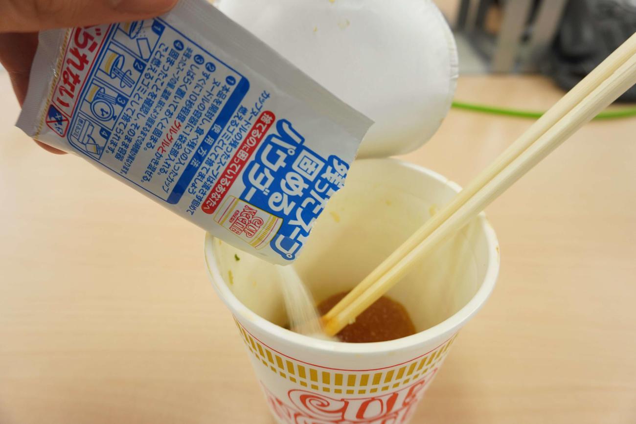 日清食品のカップヌードルに残ったスープ固めるパウダーを入れる様子(撮影・沢田直人)