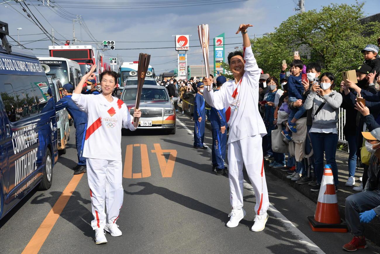 聖火ランナーを務めたNBAラプターズ渡辺雄太の母久美さん(左)と、次走者の父英幸さんはトーチキスの際にポーズを決める(代表撮影)