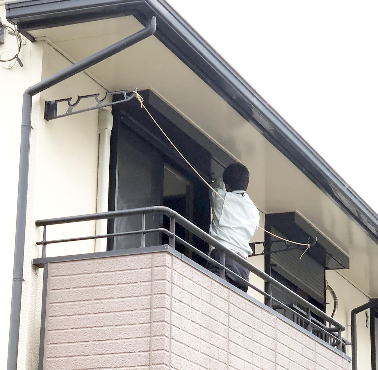 飼い主宅のベランダでアミメニシキヘビを捜す捜索員(撮影・阿部泰斉)
