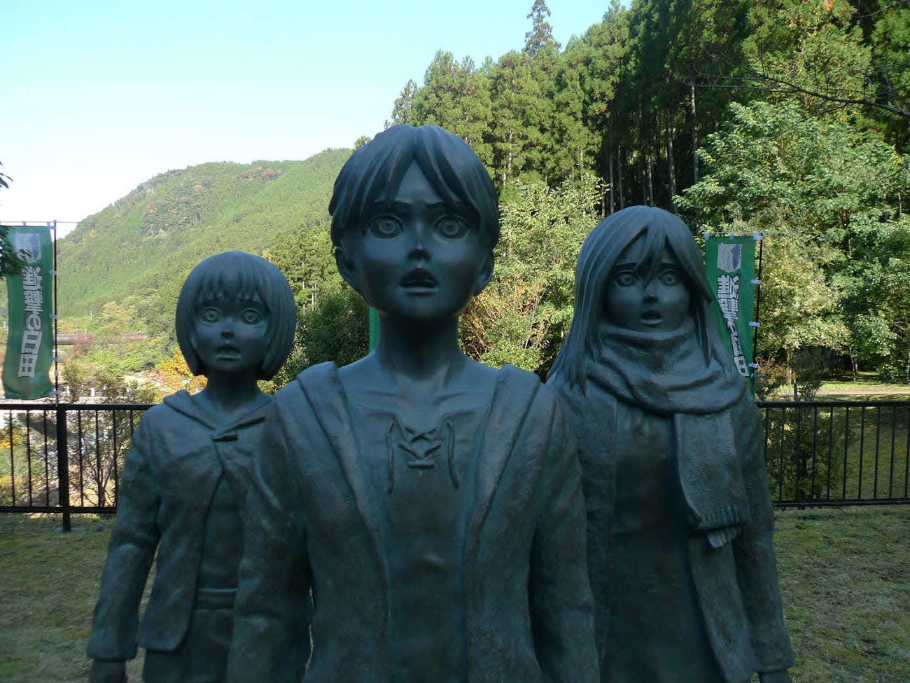 大分県日田市大山ダム下流広場に建てられた少年期のエレン(中央)ミカサ(右)アルミン(左)の銅像(進撃の日田まちおこし会議提供)