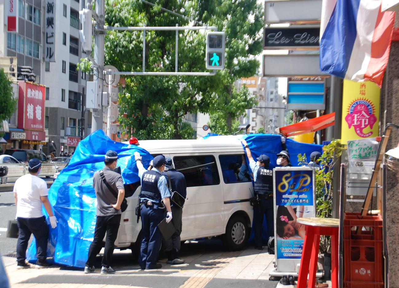 女性が倒れていたビルの前の捜査車両を青いシートで覆う大阪府警の捜査員ら(撮影・松浦隆司)