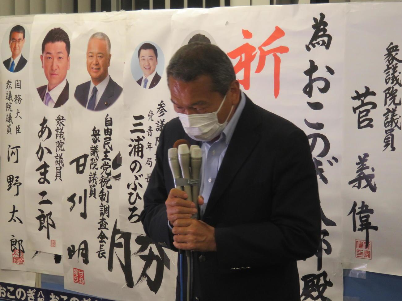 菅首相から贈られた為書きの前で頭を下げる小此木八郎氏。政界を引退することを明らかにした