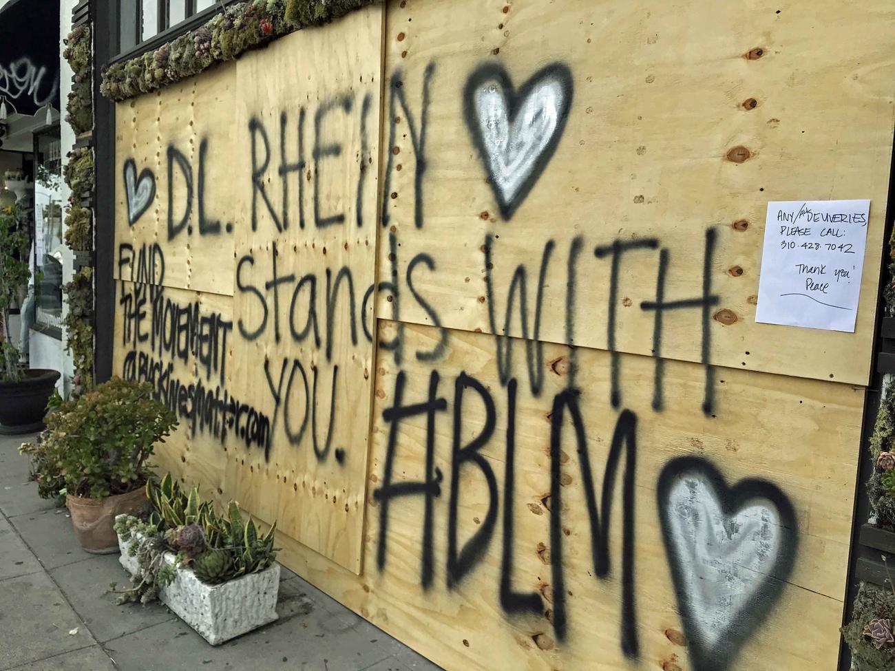 BLMサポートの文字が一面に書かれた防護板で店をプロテクトする雑貨店