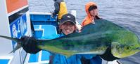 この日最大は儘田(ままだ)輝彦さんの釣った67センチだった。後方でVサインの妻千秋さんもニッコリ