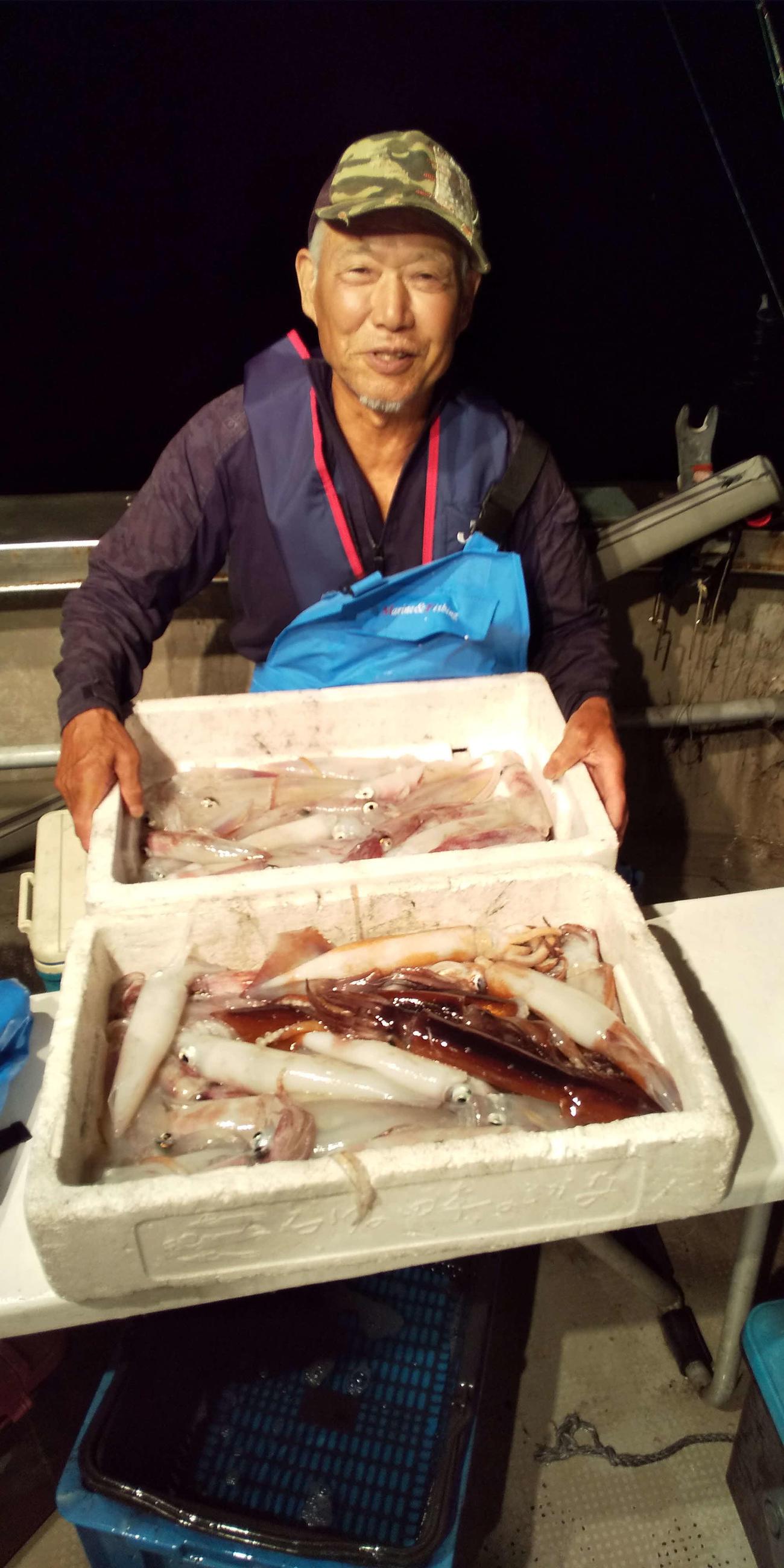 釣ったマイカを笑顔で披露する竿頭の鈴木さん