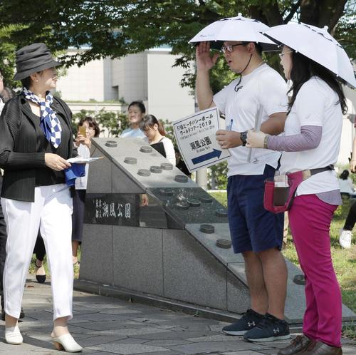 7月28日、ビーチバレーの五輪テスト大会の会場を訪れ、傘をかぶって活動するボランティア(右の2人)の様子を視察する東京都の小池知事(手前左から2人目)(共同)