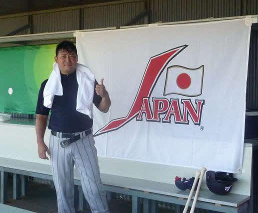 08年北京五輪野球日本代表に手伝いとして参加した光山英和氏は、日本代表のロゴの横でサムアップポーズをとる(本人提供)