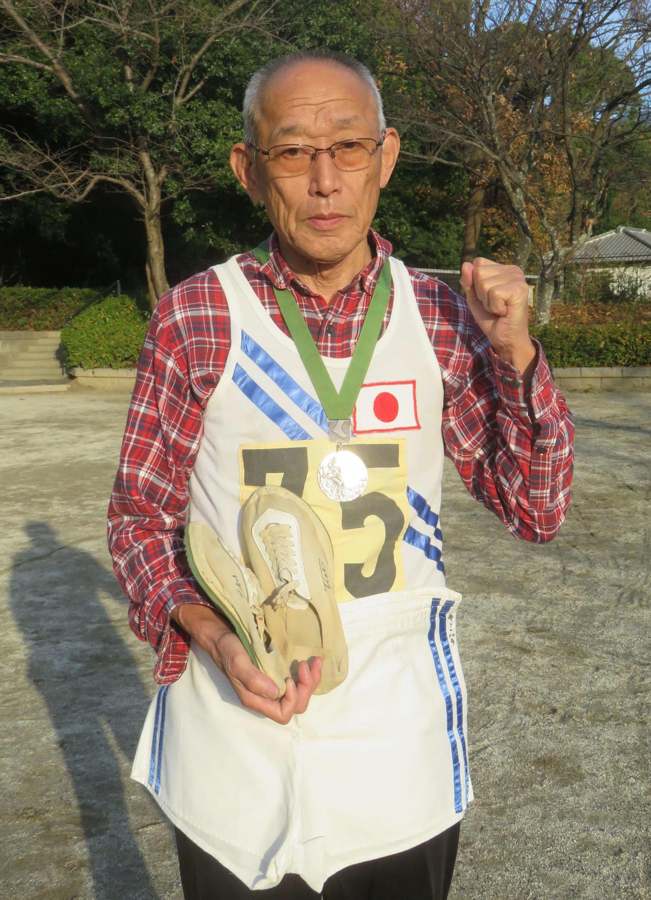君原健二さんは東京五輪時のユニホーム、シューズとメキシコ五輪の銀メダルを胸にガッツポーズ