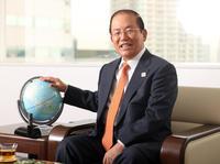 地球儀に手を添え笑顔を見せる武藤事務総長(撮影・野上伸悟)